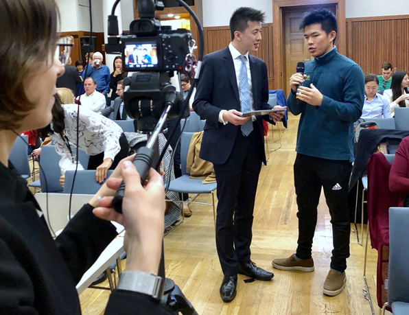 Melanie Wolzemuller filming an interview between Michael Yip (left) and LSE student Cody (right) during the conference.