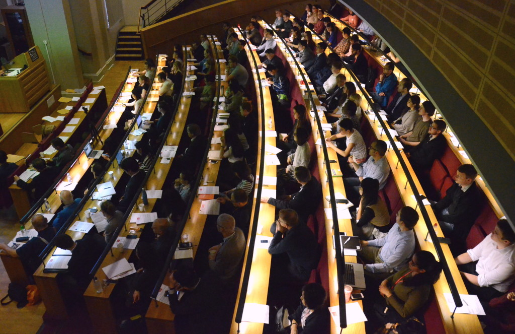 Attendees at the conference take notes during a panel discussion